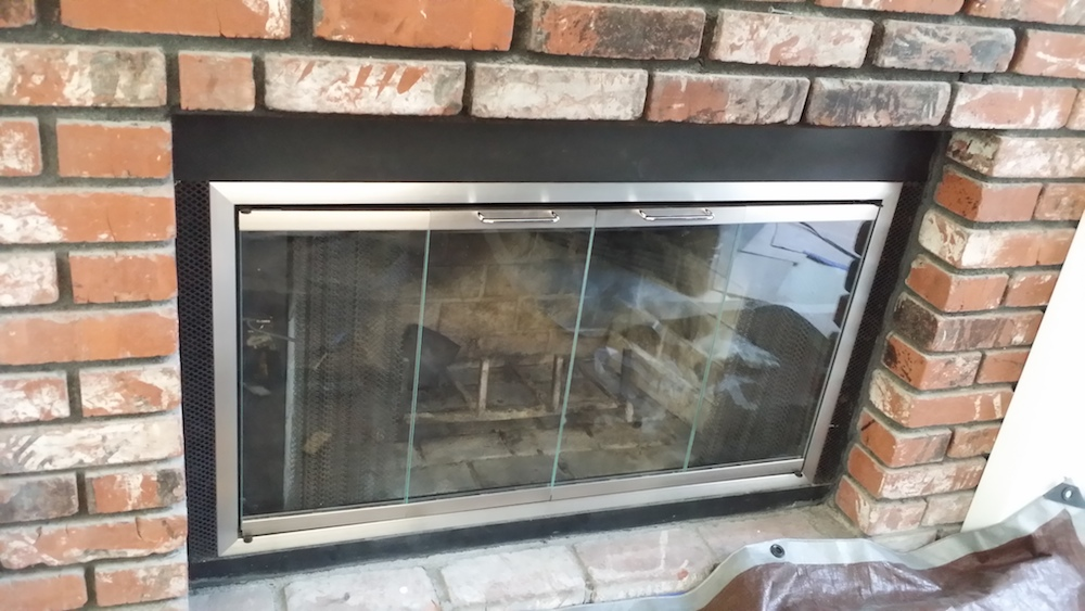 These 2 pictures are a set of custom made satin nickel finished fireplace glass doors. Gives a very nice contemporary look to an old fireplace.